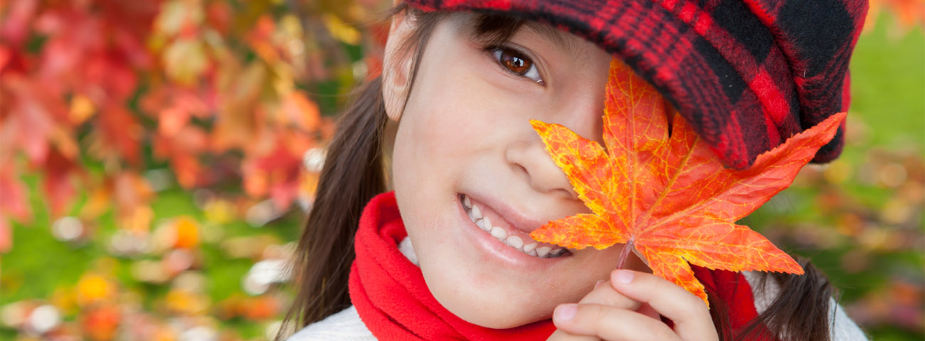 A girl covering one of her eyes with a leaf.